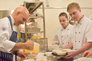Photo of chef teaching youth how to make and serve lunch