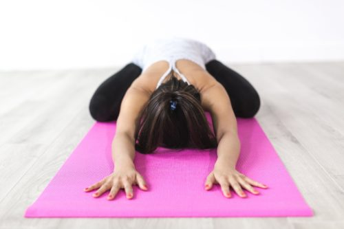 Photo of girl in child's pose on pink yoga mat