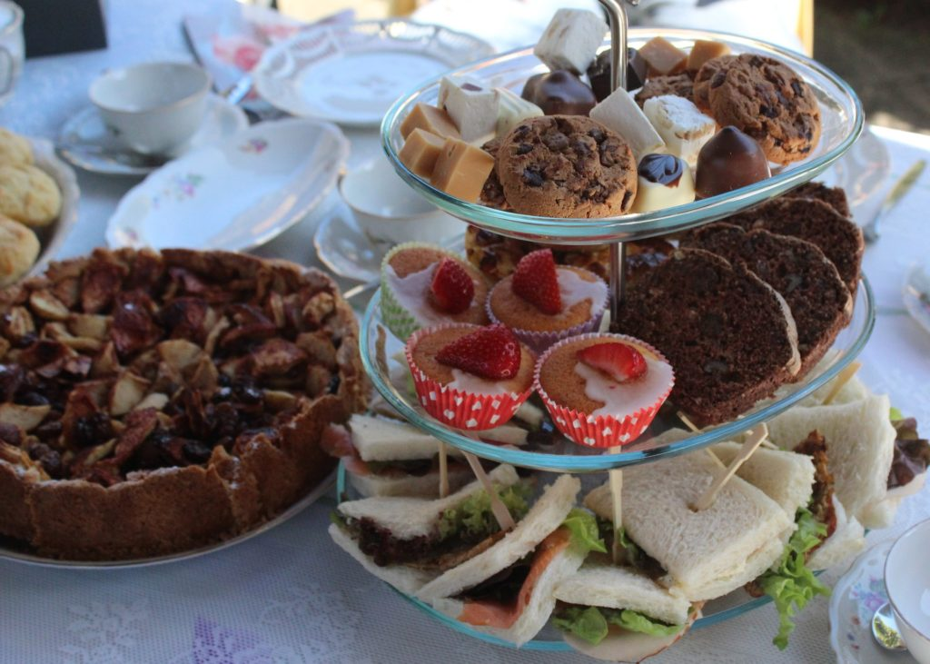 Photo of afternoon tea plates with sandwiches and cakes