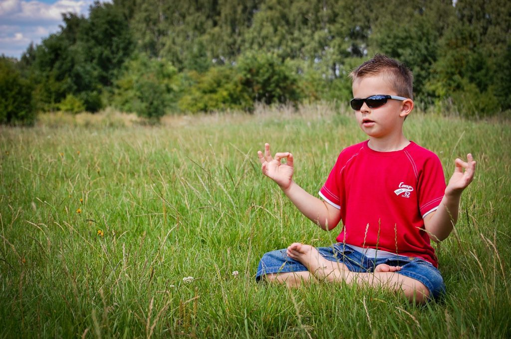 Photo of a young boy in the lotus pose