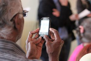 Photo of older man looking at a mobile phone